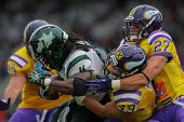 VIENNA, AUSTRIA - JULY 15 RB Tunde Ogun (#1 Dragons) is tackled by LB Simon Blach (#49 Vikings) and
