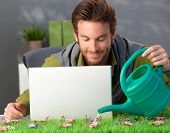 Man watering pink flowers on spring table at home, laptop computer on table.