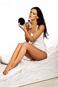 Beautiful slender brunette woman applying makeup with a large cosmetics brush and a compact mirror while sitting comfortably on her bed