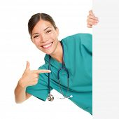 Medical sign person - woman showing blank poster billboard placard pointing. Young female nurse or medical doctor professional in green scrubs smiling happy isolated on white background.