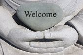image of garden sculpture  - Welcome engrained on a rock on a hand sculpture creating a welcoming and peaceful gesture - JPG