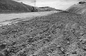 picture of sand gravel  - Excavator unloading sand at eathmoving works in construction site black and white - JPG