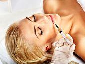 Arzt Frau Gesichts-Injektionen zu geben. Isoliert.