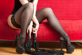 foto of sado-masochism  - The woman in black corset and stockings sitting on a red couch and holding a whip - JPG