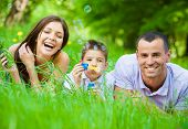 Happy family of three lying on grass while son blows bubbles. Concept of happy family relations and