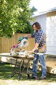 Carpenter using table saw while building deck behind home