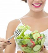 portrait of attractive  caucasian smiling woman isolated on white studio shot eating salat looking at camera