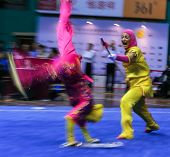 KUALA LUMPUR - NOV 05: Members of the Iranian dalian team performs a fight scene in the Women's Dual Event at the 12th World Wushu Championship on November 05, 2013 in Kuala Lumpur, Malaysia.