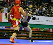 KUALA LUMPUR - NOV 05: Russia's Bektermirov Arslan (black) kicks Iran's Hamidreza Gholipour in the Sanda boxing event, 12th World Wushu Championship on November 05, 2013 in Kuala Lumpur, Malaysia.