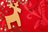 Red Christmas Background with Handmade Reindeer, Golden Stars and Ornament / copy space for your tex
