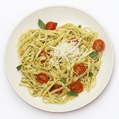 Tagliatelle ribbon pasta tossed with a green, basil pesto and grilled cherry tomatoes, garnished with basil leaves, topped with fresh-grated parmesan, viewed from above.