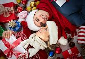 stock photo of ball cap  - Happy couple with christmas gifts relaxing at home - JPG