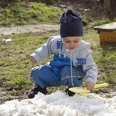 Child Playing With Snow In Spring