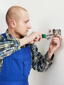 Young electrician at work with wall outlet and screwdriver installing sockets