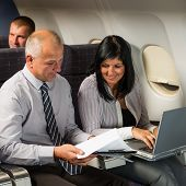 Businesspeople working on computer during flight airplane cabin passenger travel
