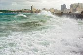 Hurricane in Havana with huge waves hitting the sea wall and a view of the skyline