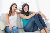 stock photo of slumber party  - Portrait of two happy relaxed young female friends sitting in the living room at home - JPG