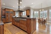 stock photo of granite  - Kitchen in luxury home with wood and granite island - JPG