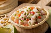 image of cilantro  - A freshly made white fish ceviche with tomato red onion cilantro red pepper lime and serrano pepper.