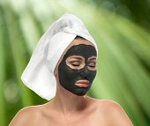 Woman receiving a mud mask on the white background. Eyes shut, looking relaxed. Skin Care in beauty