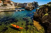 Clear water, autumn leaves and the old town walls of Dubrovnik.
