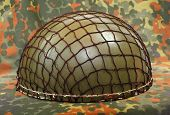 Retro military helmet ( paratrooper's helmet) on a camouflage background.