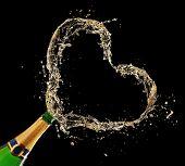 Bottle of champagne with heart shape splash on black background