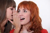 Woman whispering into another woman's ear