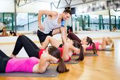 fitness, sport, training, gym and lifestyle concept - group of smiling women with male trainer doing sit ups on mats in the gym