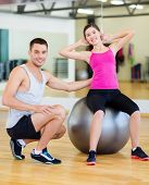 fitness, sport, training, gym and lifestyle concept - male trainer with woman doing crunches on the