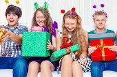 Laughing teen friends sit on the sofa with presents
