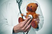 stock photo of veterinary surgery  - a doctor auscultating a teddy bear with bandages in its head and arm - JPG