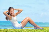 Fitness woman exercising doing sit ups outside during crossfit exercise training. Happy fit girl doing side crunches situps smiling happy. Beautiful mixed race Asian female model in grass by beach.