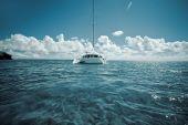 Catamaran On Calm Green Shallow Waters