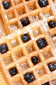 High angle shot of blueberry waffles. Closeup of waffles covered with powdered sugar and fresh blueb
