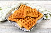 A plate of fresh made waffles on a rustic farmhouse style table.