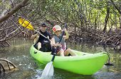 Family kayaking through tropical mangrove forest