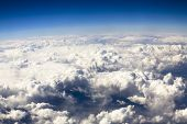 stock photo of tragic  - Blue sky and puffy clouds on height of 5000 m above Earth - JPG