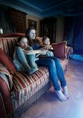 Mother With Two Daughters Watching Horror Movie At Night