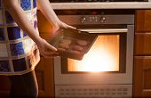 Photo Of Woman Putting Cookies In Oven