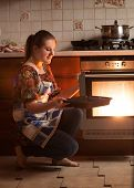stock photo of oven  - Beautiful housewife sitting next to oven and holding pan near hot oven - JPG