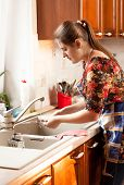 Portrait Of Woman Washing Dishes On Kitchen