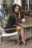 beautiful girl sitting in city cafe with cup of coffee and roses