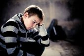 stock photo of pre-teen boy  - Portrait of Young teenager in despair against grunge background 4 light sources - JPG