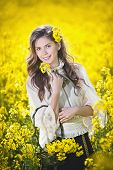 Pretty long hair girl wearing white blouse posing holding a basket in canola field, outdoor shot