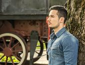 Profile Of Young Man In Denim Shirt Near Old Train, Against Tree