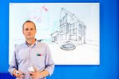 Architect, holding a white board marker, standing in front of a design sketch of a residential struc