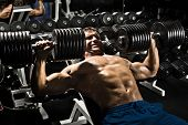 stock photo of execution  - very power athletic guy execute exercise press with dumbbells workout in sport hall - JPG