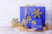 Blue holiday gift boxes and ribbon on table on wooden wall background