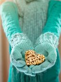 Female hands in light teal knitted mittens with entwined wooden heart . Winter and Christmas concept. St. Valentines day.